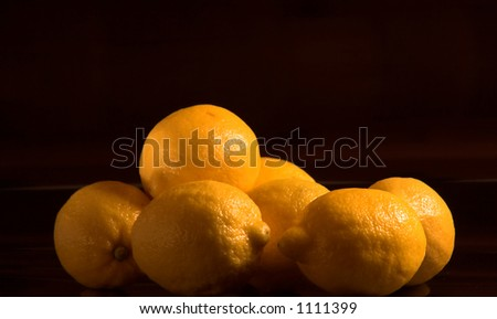 Beautiful yellow lemons isolated against a solid black background. - stock photo