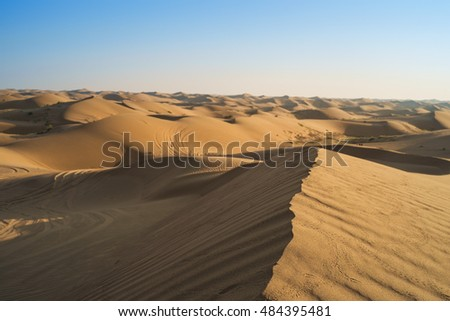 Beautiful yellow orange sand dune in desert in middle Asia with a gorgeous blue sky at sunrise.