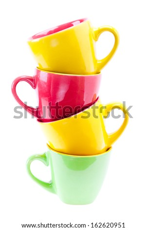 Beautiful yellow, red, green color cups. Tower stack of clean different cups isolated on white background