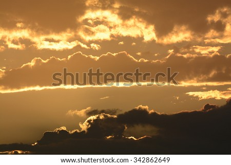 Beautiful yet moody sunrise with storm clouds in the lower thirds and reflective golden light bouncing off of the other clouds. - stock photo