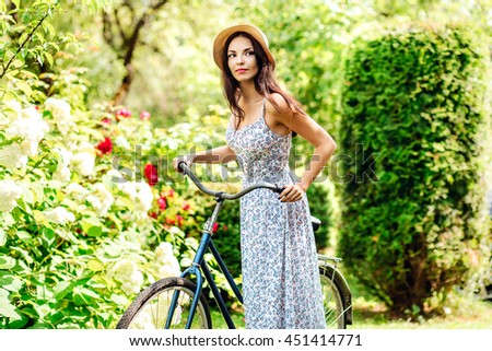 Beautiful yoang woman riding on bike on nature garden background - stock photo