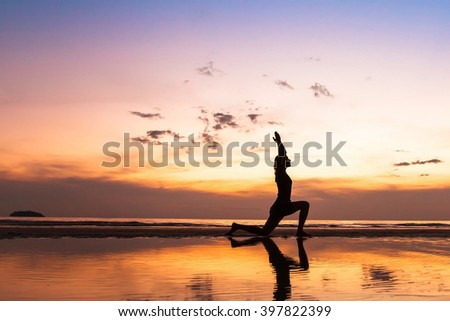 beautiful yoga exercise on the beach at sunset, background with copyspace - stock photo