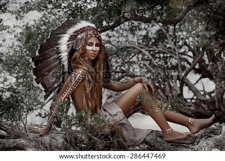 Beautiful yong woman in traditional indian headdress outdoors - stock photo