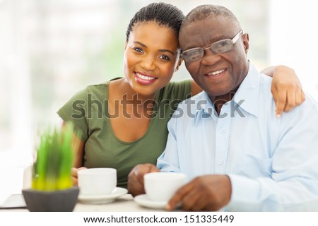 beautiful young adult african girl and father having coffee at home - stock photo