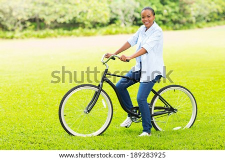 beautiful young adult african girl riding a bicycle at countryside - stock photo