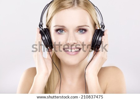 Beautiful young adult attractive sensuality blonde girl is listen to the music - stock photo