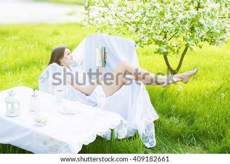 beautiful young adult caucasian girl lie with book, has rest in park cafe with cup coffee on fresh green grass and blooming tree background Slim female sit on white armchair and dreaming Closed eyes - stock photo