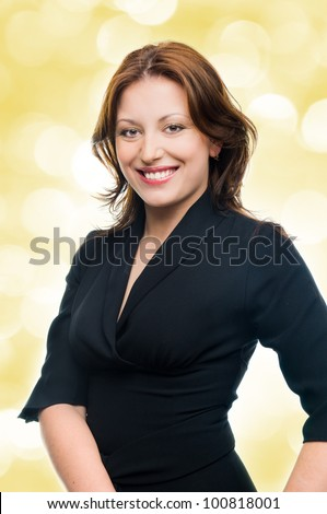 Beautiful young adult girl in black elegant dress posing  with yellow lights in the background - stock photo