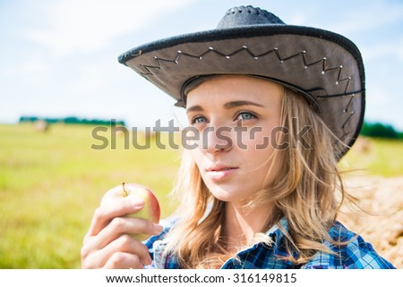 Beautiful young adult girl on hay roll background Woman hold in hand green and red fresh apple against summer grass field and blue sky with clouds Healthy natural food idea - stock photo