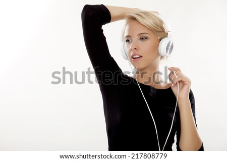 Beautiful young adult sensuality and attractive pretty blonde girl is listen to the music on the headphones isolated on white background - stock photo
