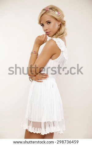 Beautiful young adult sensuality attractive and pretty blonde woman in white elegance dress and flowers in hair in studio shot - stock photo