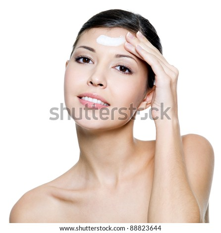 Beautiful young adult smiling female applying cosmetic cream on forehead. Isolated on white background - stock photo