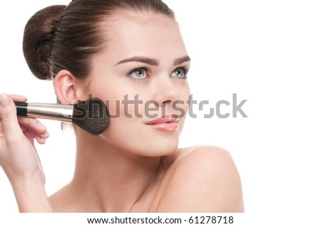 Beautiful young adult woman applying cosmetic paint brush - close-up portrait isolated on white