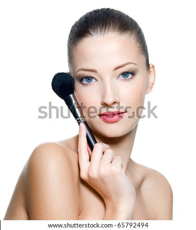 Beautiful young adult woman  holds the make-up brush for applying  rouge or powder. Fashion  model isolated on white background