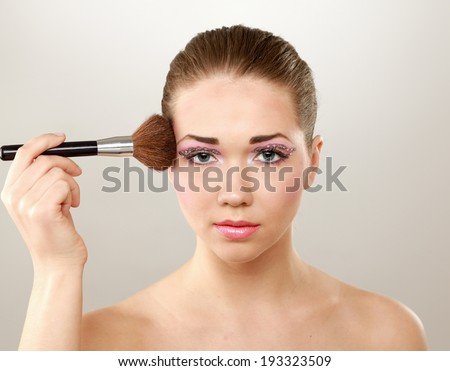 Beautiful young adult woman holds the make-up brushe near attractive face. - stock photo