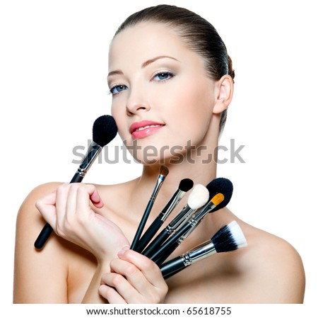 Beautiful young adult woman  holds the make-up brushes near attractive face. Fashion  model posing over white background - stock photo