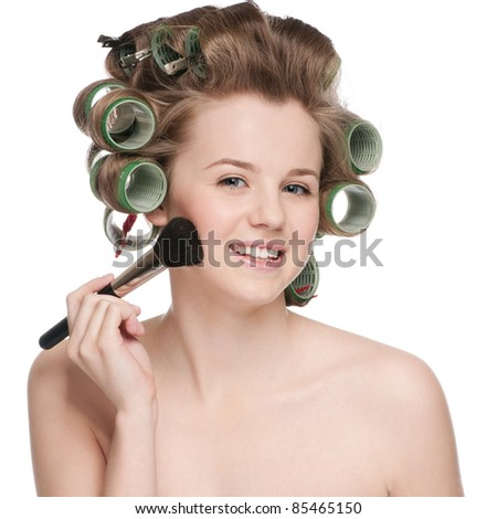 Beautiful young adult woman in hair roller applying cosmetic powder brush - close-up portrait