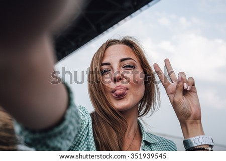 beautiful young adult woman taking picture of herself and shows tongue, selfie. - stock photo