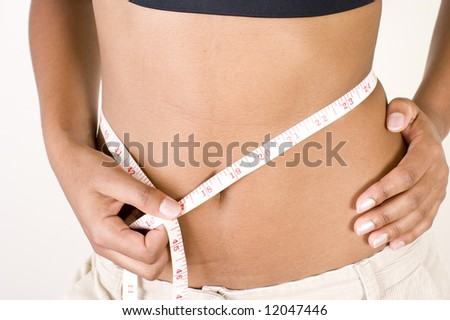 Beautiful young African adult girl with smooth chocolate brown skin, wearing a small tight black top, measuring her waist with a white measuring tape.