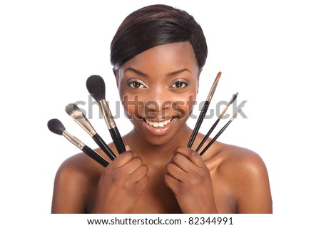 Beautiful young African American beautician woman holding set of six make up brushes. Brush types are powder blusher foundation or base, eye lash separator, brow eye shadow and eye liner brush. - stock photo