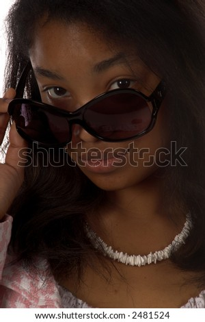 Beautiful young African American girl looking over her sunglasses - stock photo