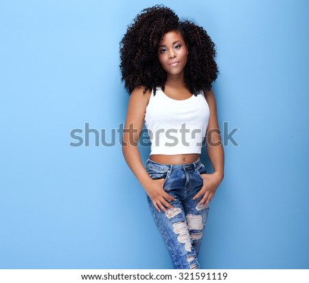 Beautiful young african american girl posing in studio, looking at camera. - stock photo
