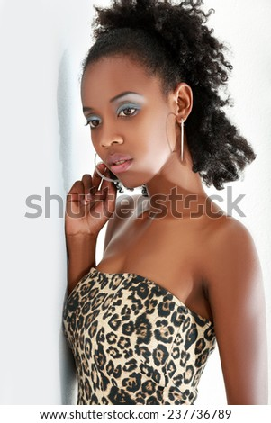 Beautiful young african american model posing against a white wall with shadow - stock photo