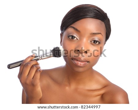 Beautiful young african american woman applying make up using stippling brush also referred to as a cosmetics powder brush. - stock photo
