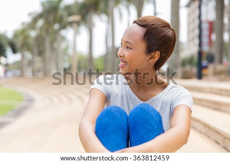 beautiful young african american woman daydreaming outdoors - stock photo
