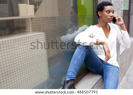 Beautiful young african american woman having a mobile phone conversation in shopping street, sitting in store window with space, city outdoors. Smart black woman using technology, lifestyle.