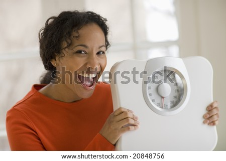 Beautiful young African American woman holding scale and shouting for joy - stock photo