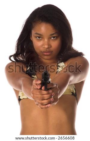 Beautiful young African American woman in a camo bikini points a 45 caliber handgun at the camera - stock photo
