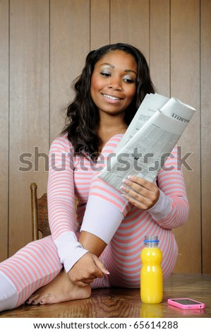 Beautiful young African-American woman in pajamas with morning paper, cell phone and orange juice - stock photo