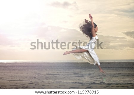Beautiful young African American woman jumping at the beach - stock photo