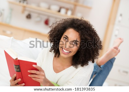 Beautiful young African American woman relaxing at home with a book lying on her stomach on a sofa smiling at the camera - stock photo