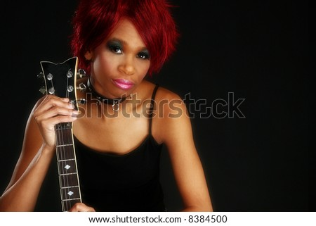 Beautiful young African American woman sitting on amp holding electric guitar over black. - stock photo