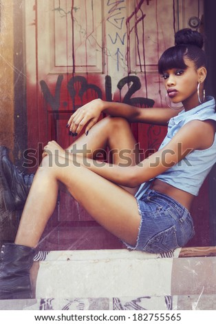 Beautiful young African American woman sitting on stoop by door wearing denim shorts and top.