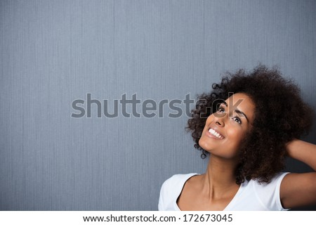 Beautiful young African American woman standing daydreaming with her hand to her curly afro hair and a whimsical smile of pleasure as she looks up into the air, with copyspace - stock photo