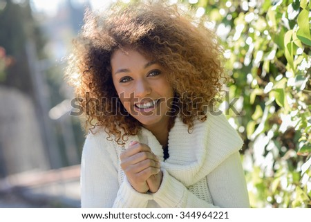 Beautiful young African American woman with afro hairstyle and green eyes wearing white winter dress with cold face