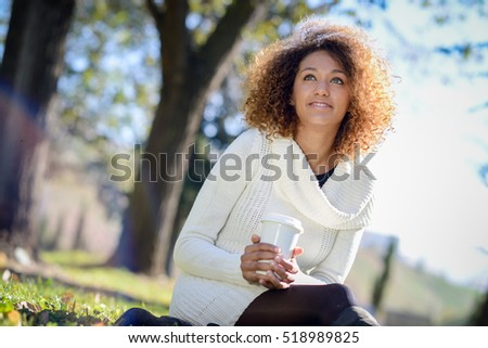 Beautiful young African American woman with afro hairstyle and green eyes wearing white winter dress. Girl drinking coffee in park sitting on grass wearing casual clothes smiling.