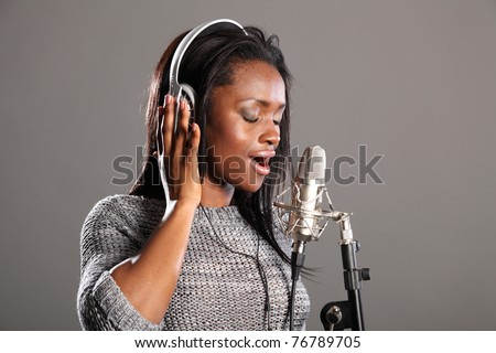 Beautiful young african american woman with eyes closed, wearing headphones and singing into microphone in recording studio. - stock photo
