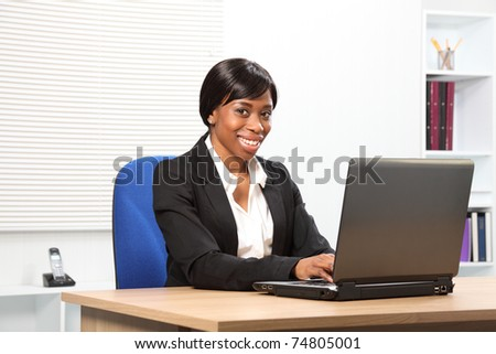 Beautiful young African American woman working in office looking up from her laptop with a lovely smile - stock photo