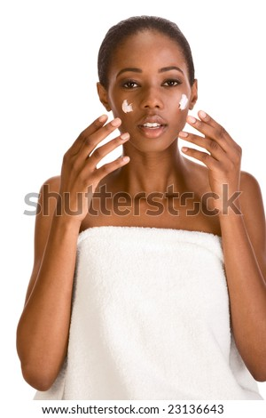 Beautiful young African American woman wrapped in bath towel with Slicked Back Hair applying moisturizer on her face - stock photo