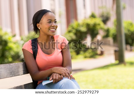 beautiful young african college students sitting on bench - stock photo