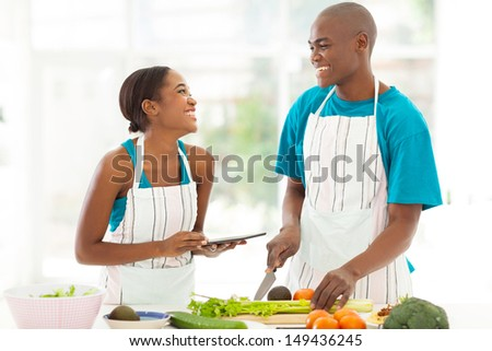 beautiful young african couple in home kitchen cooking - stock photo
