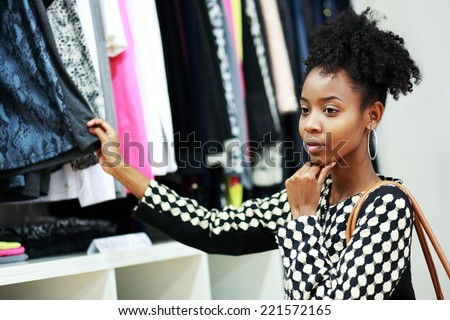 beautiful young african girl shopping in clothe's department - stock photo