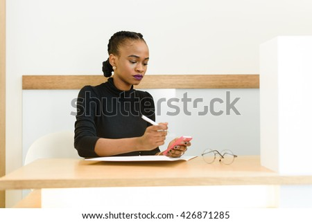 Beautiful young African or black American woman texting on mobile cellphone telephone in office - stock photo