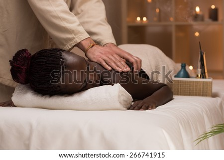 Beautiful young african woman enjoys body back massage in a luxury spa resort - stock photo