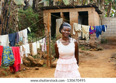 Beautiful young African woman in backyard with clothesline - stock photo