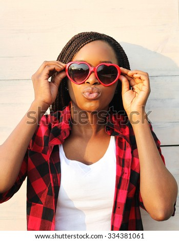 Beautiful young african woman in red sunglasses having fun  - stock photo